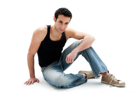 Handsome Caucasian guy wearing black tank top and jeans sitting on floor looking down, isolated