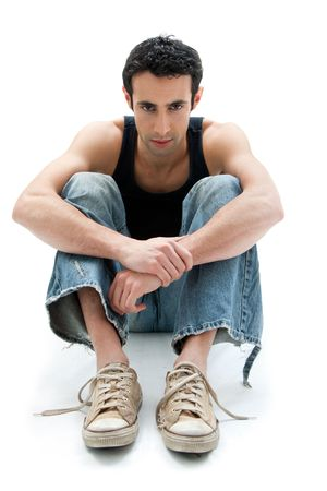 Handsome Caucasian guy wearing black tank top and jeans sitting on floor with arms around knees, isolated photo