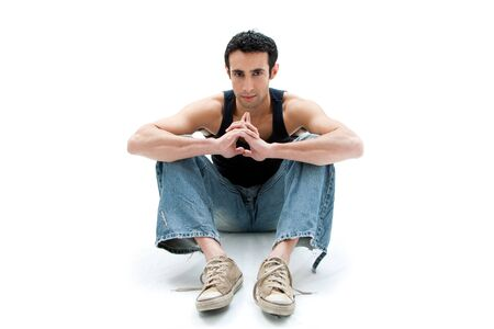 Handsome Caucasian guy wearing black tank top and jeans sitting on floor thinking, isolated photo