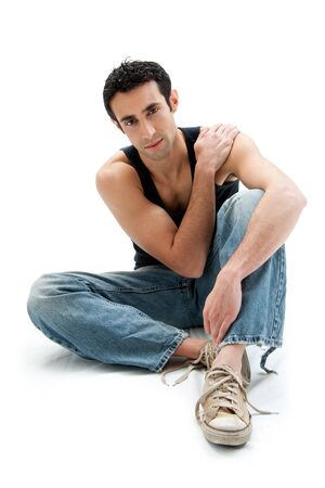 Handsome Caucasian guy wearing black tank top and jeans sitting on floor holding shoulder, isolated photo