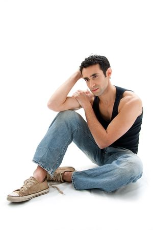 sit: Handsome Caucasian guy wearing black tank top and jeans sitting on floor thinking, isolated