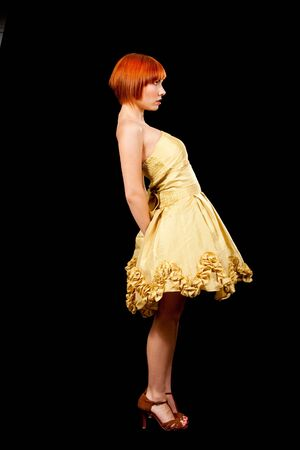 Side profile of a beautiful Caucasian redhead woman in yellow cocktail dress standing leaning backward, isolated Stock Photo