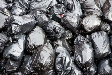 scrap heap: A pile of black garbage bags with tons of trash Stock Photo