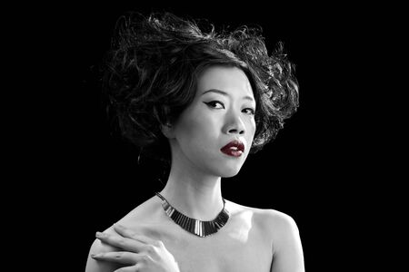 Beautiful Asian woman with red lips and bare shoulders in black and white, isolated