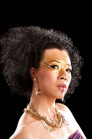 luxery: Beautiful face of an Asian woman with black curly fro hair, gold with purple makeup, bare shoulders and luxery necklace, isolated