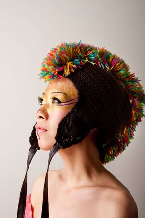 Beautiful Asian female face with a colorful mohawk hat with straps, gold and purple makeup, isolated