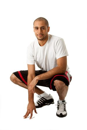 Sportief elegant Afrikaanse Hispanics man crouching en hand op verdieping, geïsoleerd