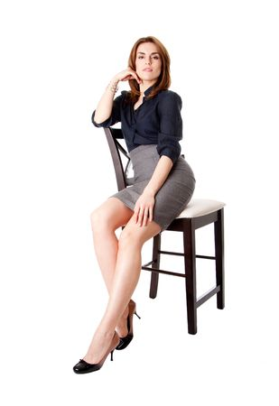 Beautiful sexy brunette business woman sitting wearing gray skirt and blue blouse with hand on leg, isolated Stock Photo - 4595961