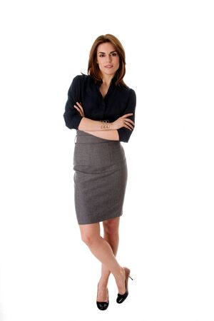 Beautiful brunette business woman standing wearing gray skirt and blue blouse with arms crossed, isolated Stock fotó