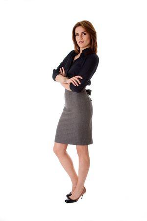 Mooie brunette zaken vrouw permanent dragen van grijze rok en blauwe blouse met armen gekruist, geïsoleerd Stockfoto