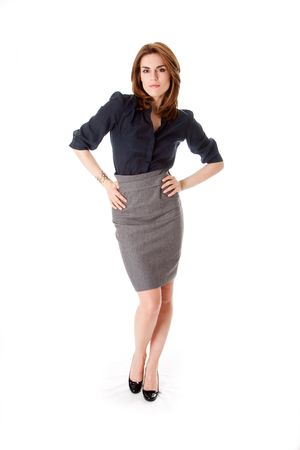 Beautiful brunette business woman with sexy attitude standing wearing gray skirt and blue blouse with hands on hips, isolated photo