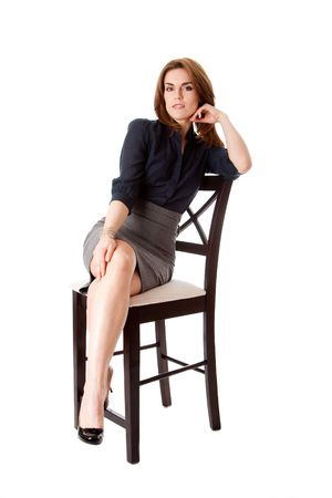 stool: Beautiful brunette business woman sitting wearing gray skirt and blue blouse with hand on leg with legs crossed, isolated Stock Photo