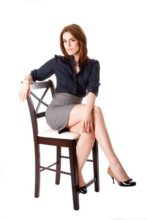 Beautiful sexy brunette business woman sitting wearing gray skirt and blue blouse with hand on leg, isolated