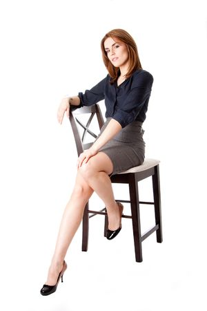 Beautiful brunette business woman sitting wearing gray skirt and blue blouse with hand on leg, isolated photo