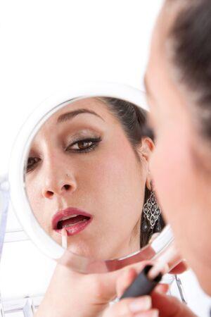 hand held: Bella donna caucasica applicando il trucco rossetto per labbra, mentre guardando in mano specchio, isolati Archivio Fotografico