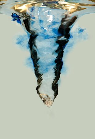 waterspout: Side view of an underwater vortex swirl with bubbles and blue ink cloud and brown tint, isolated