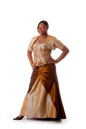 Beautiful African American woman in brown with gold dress, hands on hips and standing, isolated
