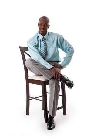 Knap African American business man lachend zittend op stoel, gekleed zee groen shirt en grijze broek, geïsoleerde Stockfoto