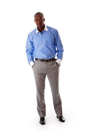 Knappe Afrikaanse Amerikaanse zaken man staan gekanteld met handen in zak, het dragen van blauwe pinstripe shirt en grijze broek, geïsoleerd