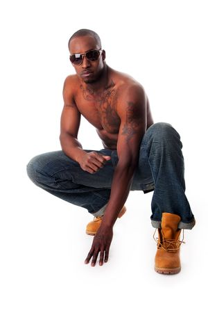 crouching: Handsome fit African American male with tough attitude squatting, toned body and tattoos, wearing blue jeans, yellow construction boots and sunglasses, isolated