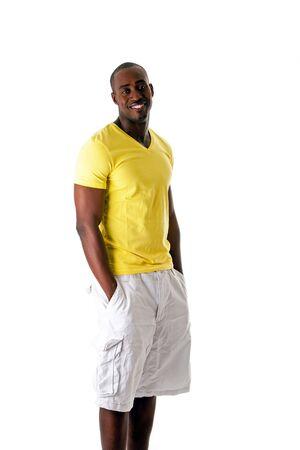 Knappe sportieve African American man in het gele overhemd en witte shorts permanent met handen in zak en grote glimlach, geïsoleerd