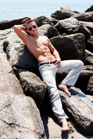 Sexy handsome male with sunglasses and toned body showing six pack abs on rocks at beach Stock Photo - 5027261