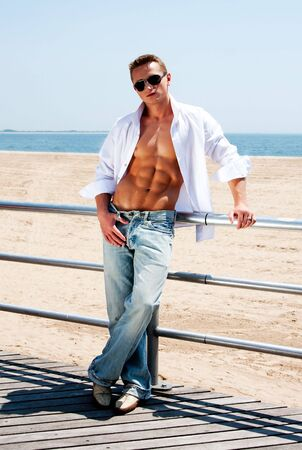 Sexy handsome male with sunglasses and toned body showing six pack abs with white shirt opne while standing next to railing on boardwalk at beach photo