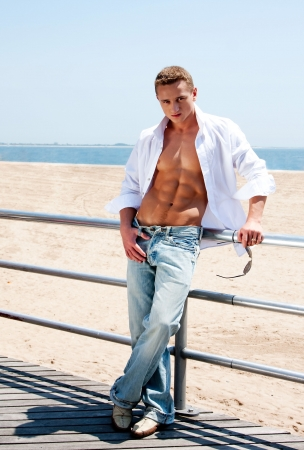 Sexy handsome male with sunglasses and toned body showing six pack abs with white shirt opne while standing next to railing on boardwalk at beach Standard-Bild