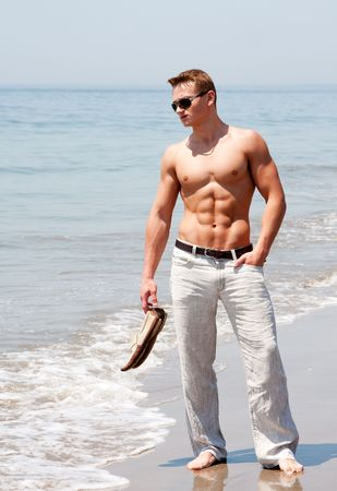 Toned cute handsome male standing on the beach with torso showing six pack abs holding shoes in hand wearing sunglasses and hand in pocket