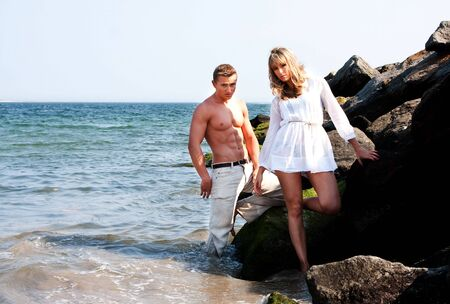 toge: Caucasian guy and girl together on rock formation next to ocean water. Female is wearing long white shirt. Both standing half in water and half on rocks at the beach. Guy showing myscular abs and bare torso wearing beige pants, heaving cool attitude. Toge