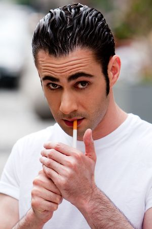 Handsome Caucasian man wearing white shirt lighting a filter cigarette, on a blurred outdoor background