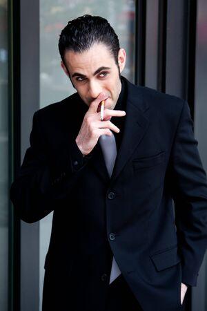 Secret surveillance photo of a Caucasian mafia business man smoking a cigarette dressed in a black suit photo