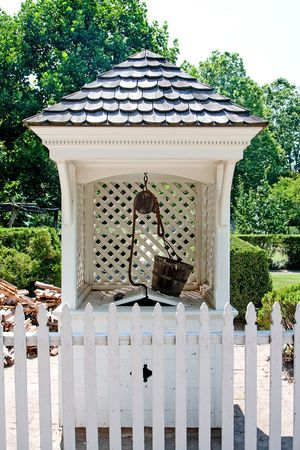 A white wishing water well in Colonial style with wooden bucket on top and roof with shingles behind a white picket fence in a garden. photo