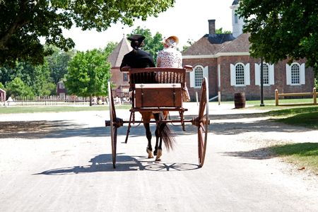 historical clothing: Rear view of a historical couple of a man and a woman dressed in Colonial American style on a brown carriage with treasure chest pulled by a horse in Colonial Williamsburg, Virginia