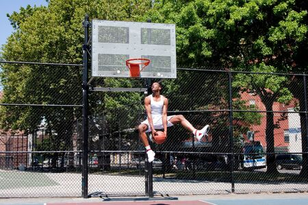 Sporty handsome African-American man dressed in white jumping in the air reaching for the basket while playing basketball in an outdoor court on a summer day