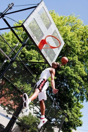 Sporty handsome African-American man dressed in white jumping in the air reaching for the basket while playing basketball in an outdoor court on a summer day trying to dunk the ball photo