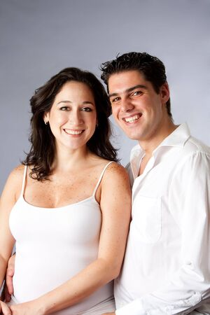 engaged: Portrait of a beautiful happy young couple smiling dressed in white, isolated
