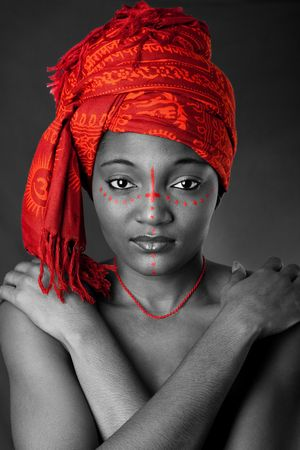 traditional: Beautiful traditional African-American woman wearing a authentic tribal red orange head scarf and red dotted makeup, heaving arms crossed on chest, isolated.