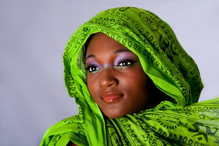 sincere girl: The face of an innocent beautiful young African-American woman with green headwrap and purple-green makeup, isolated Stock Photo