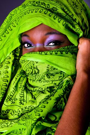 The face of an innocent beautiful young African-American woman covering her mouth showing only her eyes with green headwrap and purple-green makeup, isolated
