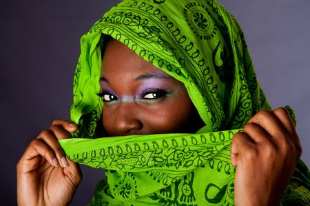hands covering face: The face of an innocent beautiful young African-American woman covering her mouth with green headwrap and purple-green makeup, isolated