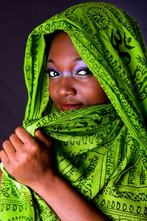 sincere girl: The face of an shy innocent beautiful young African-American woman covering her mouth with green headwrap and purple-green makeup, isolated