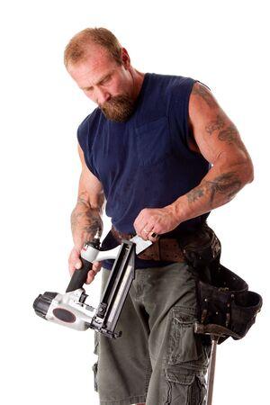 Sterke man met tatoeages het laden van een spijker pistool met nagels, het dragen van een gordel met gereedschap hamer, geïsoleerde