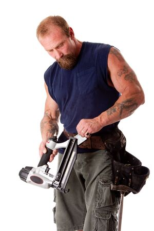 Strong man with tattoos loading a nail gun with nails, wearing a tool belt with hammer, isolated photo