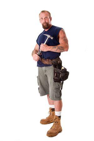 Grote blanke man met tatoeages stond met hamer in zijn handen en het dragen van een instrument gordel, geïsoleerd.
