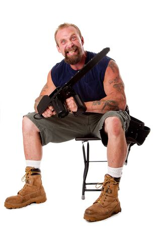 Crazy Caucasian man with tattoos and chainsaw sitting on stool with strong facial expression, isolated. Stock Photo - 5446880