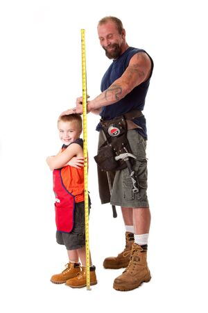 Father wearing tool belt with toy hammer and measuring tape, measures height of cute son dressed in orange apron, isolated. Stockfoto