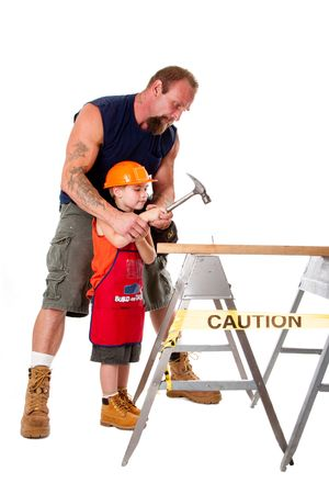 Caucasian father teaching his cute son how to hold a hammer and hit a nail into a wooden plank, isolated. photo