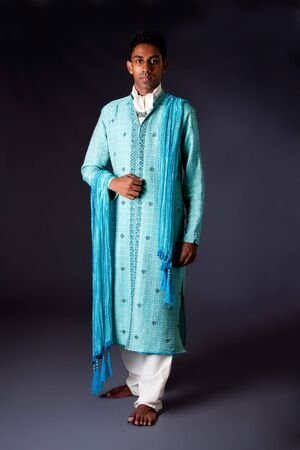 Beautiful authentic Indian hindu man in typical ethnic groom attire. Bengali male wearing a light blue agua decorated Dhoti with shawl. 版權商用圖片 - 5466673