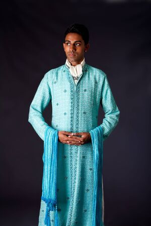 dhoti: Beautiful authentic Indian hindu man in typical ethnic groom attire standing with hands together. Bangali male wearing a light blue agua decorated Dhoti with shawl.